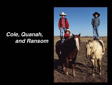 Cole and Ransom standing on the backs of their horses; Quanah sits in front of Cole.